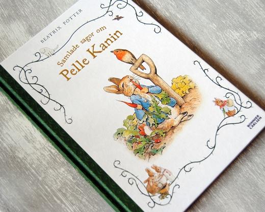 Omslagsbild Samlade sagor om Pelle Kanin: en kanin i blå jacka som äter morötter, en rödhake som sitter på skaftet till en spade.